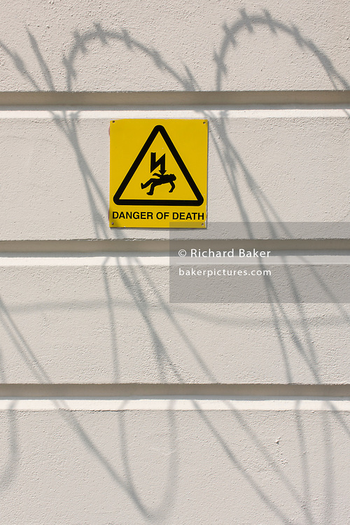The shadows of razor-wire is seen with a Danger of Death sign, on a white perimeter wall of the All England Tennis Club, Wimbledon.