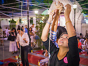 "31 DECEMBER 2012 - BANGKOK, THAILAND: Women tie New Year's blessing to a string at Wat Pathum Wan next to Central World in Bangkok. Many Thais go to Buddhist temples and shrines to ""make merit"" for the New Year. The traditional Thai New Year is based on the lunar calender and is celebrated in April, but the Gregorian New Year is celebrated throughout the Kingdom, especially in larger cities and tourist centers, like Bangkok, Chiang Mai and Phuket. The Bangkok Countdown 2013 event was called ?Happiness is all Around @ Ratchaprasong.? All of the streets leading to Ratchaprasong Intersection were closed and the malls in the area stayed open throughout the evening.    PHOTO BY JACK KURTZ"