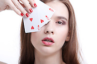 Portrait of beautiful young woman covering her eyes with playing cards against white background