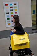 A woman shopper carrying a yellow bag from Selfridges department store walks past a colour swatch on the wall of a central London business, on 22nd November 2017, in London England.