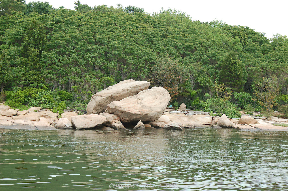 A huge bolder on one of the Thimble Islands in Long Island Sound at Stone Creek, CT.  The boulder is split as though cut by a knife.