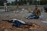 Makiivka, Ukraine - August 19, 2014: A mother is supported by her son, a pro-Russian rebel, as she despairs in front of the body of her daughter, who died next to two other people by a grocery shop after an intense morning shelling by Ukrainian troops near a railway in Makiivka, some 15km east of Donetsk. CREDIT: Photo by Mauricio Lima for The New York Times
