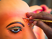 "29 AUGUST 2016 - BANGKOK, THAILAND:  A craftsman at the Vishnu Temple in Bangkok paints the face of a statue of Ganesha, an important Hindu deity known as the ""overcomer of obstacles."" Ganesha Chaturthi is the Hindu festival celebrated on the day of the re-birth of Lord Ganesha, the son of Shiva and Parvati. Ganesha is widely revered as the patron of arts and sciences and the deva of intellect and wisdom. The last day of the festival is marked by the immersion of the deity in nearby bodies of water. The immersion symbolizes the cycle of creation and dissolution in nature. The deities made at the Vishnu Temple in Bangkok will be submerged in rivers and streams across Thailand at several Ganesha festivals held in September.           PHOTO BY JACK KURTZ"