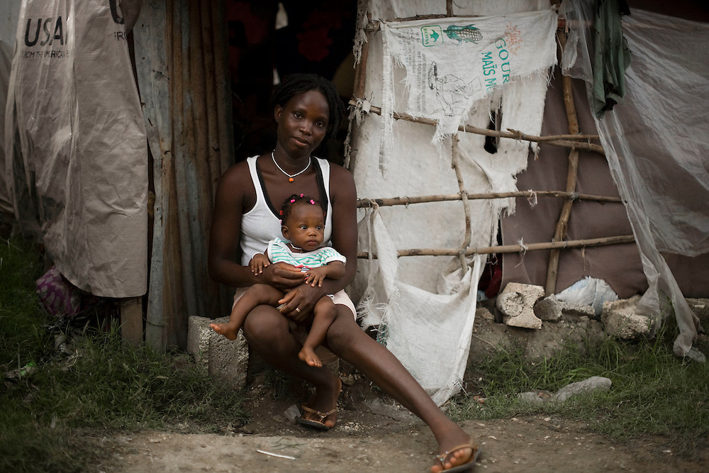 "Gracieuse Jean, and her daughter Daphene Aristène sit in the doorway of their shelter. Daphene Aristène, 6 months, was born in Santo, on the outskirts of Port-Au-Prince during the earthquake on January 12th. .Her mother, Gracieuse Jean, went into labor at 4 PM on the 12th. She ran outside when her house started shaking and while her house collapsed completely, she gave birth to Aristène at 6 PM in the street. Gracieuse also has two boys, aged 4 and 5. Her husband has been out of work since the earthquake. The whole family has been staying in a shelter made from tarps since the earthquake. Daphene Aristène's nickname is ""Goudou Goudou"" which is a Haitian Creole slang term for earthquake."