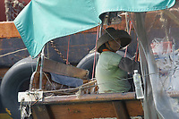 Tanka fisherman on a fishing boat at Aberdeen floating village, Hong Kong, Hong Kong, August 2008   Photo: Peter Llewellyn