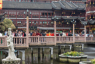 Shanghai, China--March 30, 2016. Shanghai is packed with shoppers in an outdoor mall type setting, elevated above water.