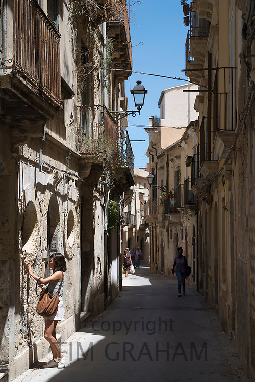 Street scene woman touching old stone in ornate alleyway Via Dione in Ortigia, Syracuse, Sicily