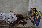 The body of an Egyptian Coptic Christian man is seen near religious icons left by mourners October 10, 20011 at the Coptic Hospital morgue in Cairo, Egypt. At least 26 people, mostly Christian, were killed a day earlier during sectarian clashes that saw the worst violence since the Revolution that toppled former Egyptian president Hosni Mubarak earlier this year. Egyptian Coptic Christians make up about 10% of Egypt's 80 million population and periodically violence flares between the Christian minority and the majority Muslim population. (Photo by Scott Nelson)