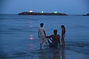 A rock off Nagoa Beach lights up a sign of 'Diu' as the sun sets. Nagoa Beach is a popular tourist destination.