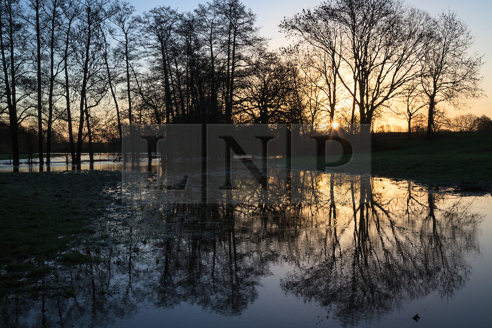 © Licensed to London News Pictures. 02/01/2014. River Blackwater, Hampshire, UK. Sunrise reveals flooding on the River Blackwater at Wade Bridge near Romsey in Hampshire, UK. River levels are high following a night of wet and windy weather. More wet and windy weather is forecast. Photo credit : Rob Arnold/LNP