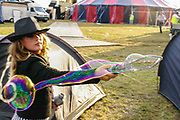A girl plays with large bubbles in the festival, Boomtown, Matterley Estate, Alresford Road, near Winchester, Hampshire, UK, August, 2010