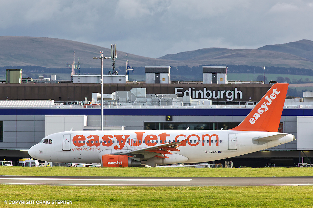An Easyjet Plane on the tarmac at Edinburgh airport with the terminal to the rear