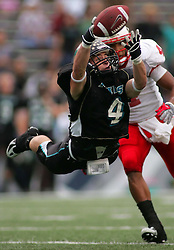 Pasadena Memorial's Bo Snelson (4) makes a leaping reception past Katy's Trent Hunter during the Dragons' 30-14 playoff loss to the Tigers, December 1, 2007, at Rice Stadium in Houston.