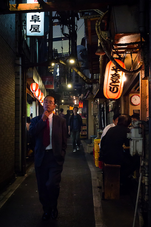 Near Shinjuku station, on an alley filled with yakitori restaurants, a man walks by looking for a place to dine after work.