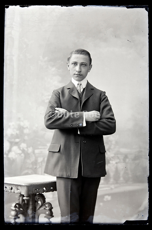 vintage studio portrait of a young adult man standing with folding arms circa 1920s