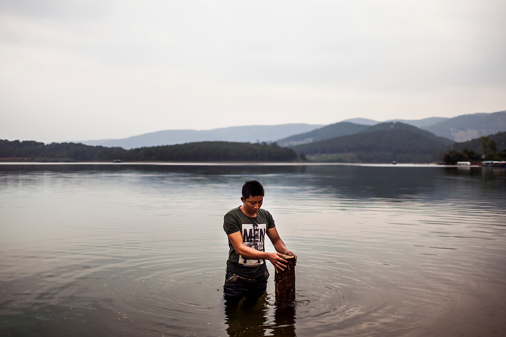 A young man stands in a lake in Dalat, Vietnam.