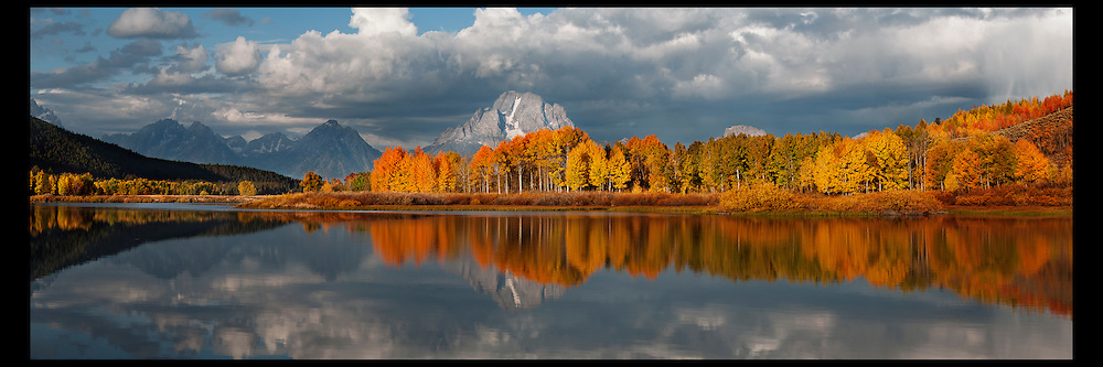 Prime foliage time at iconic Oxbow Bend in Grand Teton National Park. Mount Moran and peak aspens are reflected in the calm waters of the Snake River.