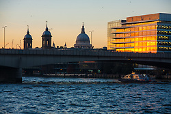 London, November 24th 2014. With London having enjoyed a clear if cold day, weather forecasters are predicying a cold night with temperatures expected to dip as low as 3 degrees in the early hours of Tuesday. PICTURED: The last rays of the sun illuminate an office block on the Thames asn people amke their way across London Bridge.