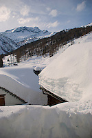 Ticino, Southern Switzerland. Snow-covered rooves in Bosca Gurin with a mountain backdrop.