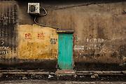 Tuquoise door opens on a grey facade, Man Xa Village, Northern outskirts of Hanoi, Vietnam, Southeast Asia