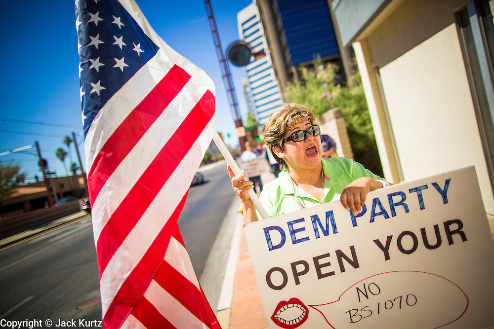 08 JUNE 2012 - PHOENIX, AZ:   LILIA HUERTA, from Phoenix, pickets the Arizona Democratic party headquarters. About 30 members of the Arizona Democratic Party picketed party headquarters Friday to show their unhappiness with party leadership. They claim the party, or party endorsed candidates, is accepting money from the American Legislative Exchange Council (ALEC) and is not properly supporting Democratic candidates not endorsed by the party, even during the primaries.            PHOTO BY JACK KURTZ