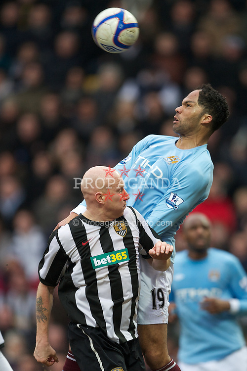 NOTTINGHAM, ENGLAND - Sunday, January 30, 2011: Manchester City's Joleon Lescott and Notts County's Lee Hughes during the FA Cup 4th Round match at Meadow Lane. (Photo by David Rawcliffe/Propaganda)