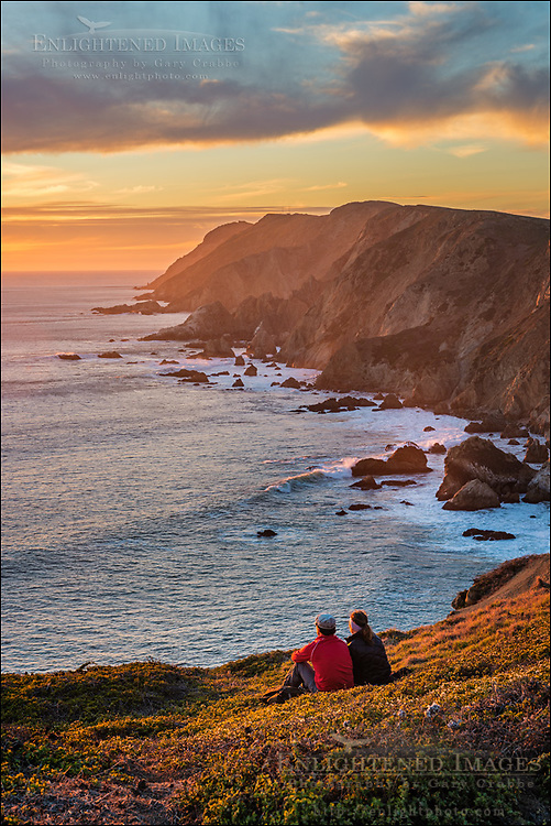 Couple watching the sunset along the headland cliffs at Point Reyes National Seashore, Marin County, California