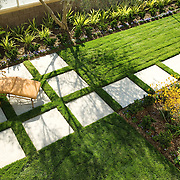 high angle view of residential backyard with late afternoon sun lighting green lawn, chaise and large concrete pavers.
