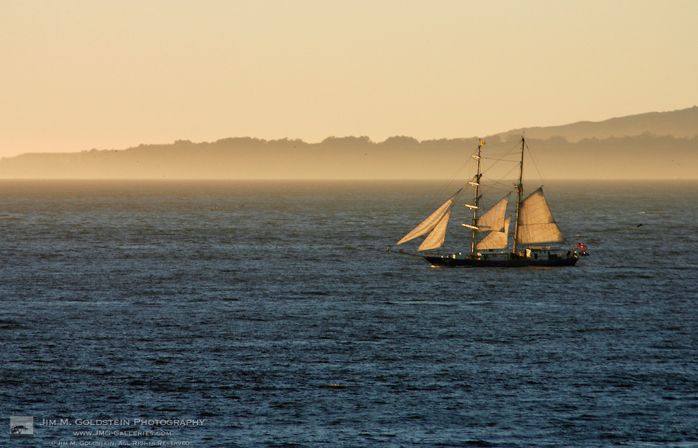 A large sailboat heads out to sea from San Francisco, California at sunset