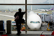 Asia, Southeast, People's Republic of China, Hong Kong, Silhouette of a man waiting for the flight at Hong Kong international airport.