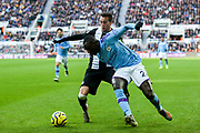 Javi Manquillo (#19) of Newcastle United steals the ball from Benjamin Mendy (#22) of Manchester City on the edge of the penalty box during the Premier League match between Newcastle United and Manchester City at St. James's Park, Newcastle, England on 30 November 2019.