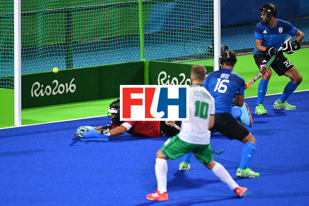 Ireland score past Argentina's Juan Vivaldi (L) during the mens's field hockey Ireland vs Argentina match of the Rio 2016 Olympics Games at the Olympic Hockey Centre in Rio de Janeiro on August, 12 2016. / AFP / Carl DE SOUZA        (Photo credit should read CARL DE SOUZA/AFP/Getty Images)