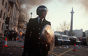 Riot police officers stand firm in Trafalgar Square at the height of the Poll Tax Riot on 31st March 1990, in Westminster, London, England. Angry crowds, demonstrating against Margaret Thatcher's local authority tax, stormed the Whitehall area and then London's West End, starting fires and overturning cars, looting stores up Charing Cross Road and St Martin's Lane. The anti-poll tax rally in central London erupted into the worst riots seen in the city for a century. Forty-five police officers were among the 113 people injured as well as 20 police horses. 340 people were arrested.