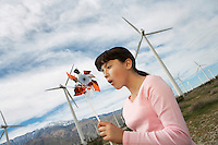 Girl (7-9) playing with toy windmill at wind farm