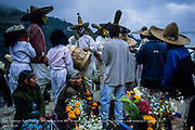 """Day of the Dead celebrations, the village's market. The Dia de Muertos (Day of the Dead), recently declared by UNESCO as an """"oral and intangible cultural heritage of humanity,"""" is one of Mexico's most cherished traditions, celebrated in cities and villages countrywide. Far away from more well-traveled tourist routes, in a Sierrra Madre mountain village near Oaxaca, women speak quietly with beloved departed souls at graves adorned with offerings of food, candies, liquor, cigarettes, evertything their dead  enjoyed while alive. In Huautla de Jimenez local Mazatec Indians still meet their long-gone friends and family in the graveyard, celebrating along with Huehuetones, mysterious masked figures representing the visiting souls from the Underworld."""
