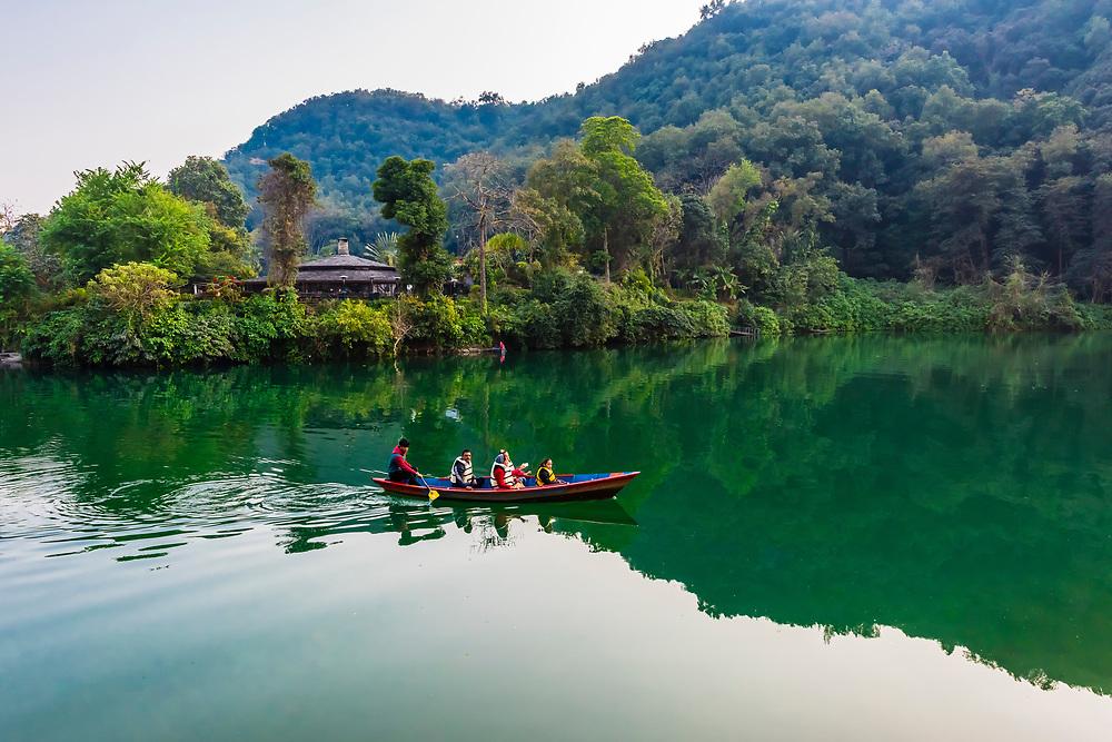 A rowboat brings people across to the Fishtail Lodge, Phewa Lake, Pokhara, Nepal.