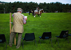 © Licensed to London News Pictures.29/08/15<br /> Bilsdale, UK. <br /> <br /> A man stands and reads the events programme during the 105th Bilsdale Country Show in North Yorkshire.<br /> <br /> Photo credit : Ian Forsyth/LNP