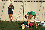 As a competitor stays warm under a black bin liner in the sun, another runner rubs his calf muscles before the mass start of the London Marathon in Greenwich Park, on 21st April 1991, in London, England.