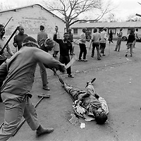 September 17, 1990. Nancefield Hostel, Soweto, South Africa. Zulu Inkatha supporters club and stab a man believed to be an African National Congress supporter to death. Photo Greg Marinovich