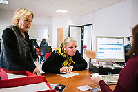 "NAPLES, ITALY - 9 NOVEMBER 2018: Lucia Messina (58, center), an unemployed citizen,  registers to the Eastern Naples Job Center, accompanied by his mother, in Naples, Italy, on November 9th 2018.<br /> ""I want to sign-up because I'm looking for a job, but also for the ""citizens' wage"""", she said.<br /> <br /> Italy's 550 state-run job centers will be in charge of verifying that recipients of the ""citizens' wage"", a welfare policy championed by the governing 5-Star Movement designed to lift 5 million Italian out of poverty, meet an important eligibility criteria: that they are actively looking for a job.<br /> But Italians widely regard the centers as being blighted by obsolete technology and insufficient and under-qualified staff. The new populist government plans to spend 1 billion euros to modernize the centers — 10 percent of the total cost of the new policy in its first year in 2019. <br /> <br /> The ""citizens' wage"" will cost 10 billion euros next year, the most expensive item in a big-spending budget which itself has raised concerns in the European Union that Italy could be sowing the seeds of a financial crisis."