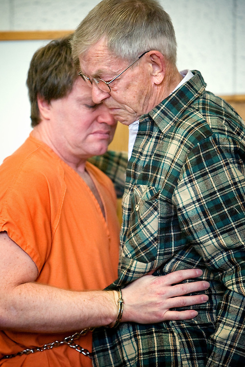 JEROME A. POLLOS/Press..Edmund Bergeman hugs his father, Richard Bergeman, before being escorted from the courtroom Tuesday where he pled guilty under an Alford plea to two counts of lewd conduct with minors, one charge of raping an unconscious woman and possession of child pornography. Bergeman will serve 20 years to life in prison for his actions in Kootenai County's largest-ever child pornography case.