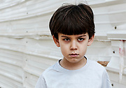 angry young boy of six outdoors near a closed off construction site