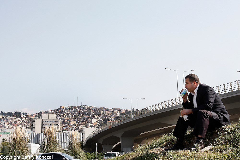 A man sits near an overpass for a snack in Izmir, Turkey