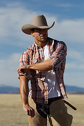 cowboy out in a field rolling up his sleeves