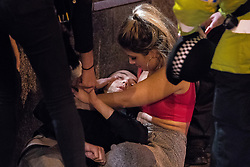 """© Licensed to London News Pictures . 16/12/2017. Manchester, UK. A man, understood to be injured, is tended to by a woman and police , on Peter Street . Revellers out in Manchester City Centre overnight during """" Mad Friday """" , named for historically being one of the busiest nights of the year for the emergency services in the UK . Photo credit: Joel Goodman/LNP"""