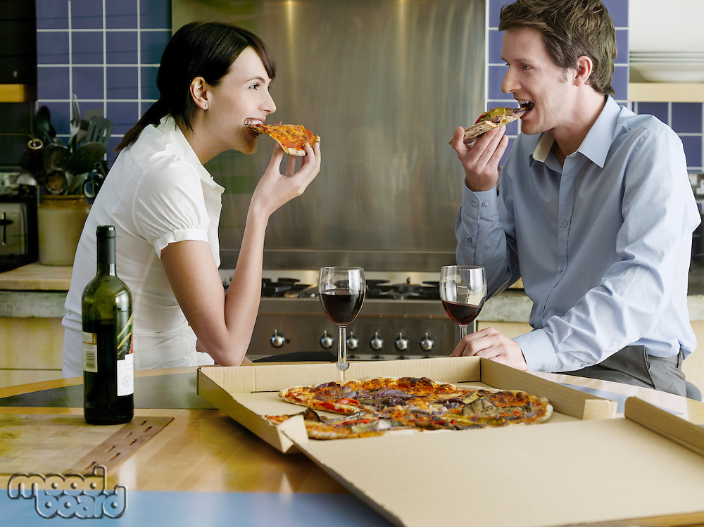 Young couple eating pizza in kitchen