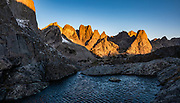 "Sunrise on Pingora Peak seen from Jackass Pass, Cirque of the Towers, Bridger Wilderness, Wind River Range, Bridger-Teton National Forest, Rocky Mountains, Wyoming, USA. We backpacked to Big Sandy Lake Campground (11 miles round trip with 1000 feet gain). Two hours before sunrise, I departed from Big Sandy Lake to reach Jackass Pass viewpoint for Cirque of the Towers and Lonesome Lake (6.5 miles round trip, 1860 ft gain) on the Continental Divide Trail. The Continental Divide follows the crest of the ""Winds"". Mostly composed of granite batholiths formed deep within the earth over 1 billion years ago, the Wind River Range is one of the oldest mountain ranges in North America. These granite monoliths were uplifted, exposed by erosion, then carved by glaciers 500,000 years ago to form cirques and U-shaped valleys. This image was stitched from multiple overlapping photos."