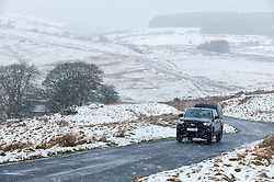 © Licensed to London News Pictures. 28/02/2017. Mynydd Epynt, Powys, Wales, UK. A motorist drives on the high moorland of the Mynydd Epynt range as driving wind and snow hits the high land in Powys, Wales, UK. About 6cm of snow fell last night on high land. Photo credit: Graham M. Lawrence/LNP