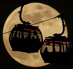 Emirates Air Line cable cars are silhouetted against the backdrop of a 'Super Snow Moon' in Greenwich, London.