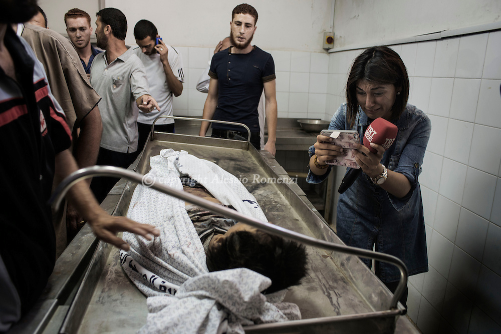 Gaza Strip, Gaza City: A journalist react inside the morgue of the Shifa hospital in Gaza City over the body of one of four boys, all from the Bakr family, killed by Israeli naval bombardment in the port of Gaza City, on July 16, 2014. . ALESSIO ROMENZI